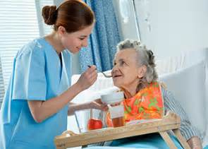 Caregiver feeding female senior at nursing home, caregiver, nursing home, senior