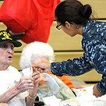 Caregiver helping seniors at nursing home, age in place, military, couple